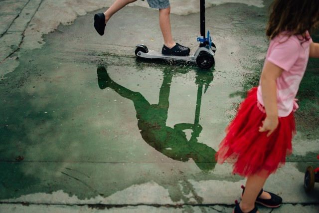 Child scooting through a puddle