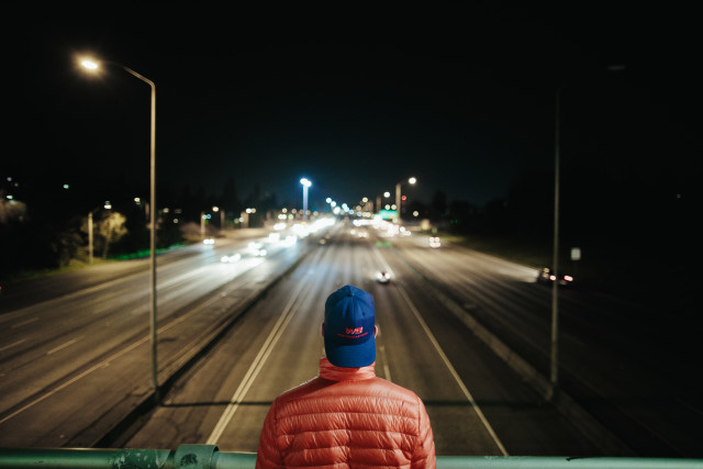Man with a blue hat looks out on an almost deserted highway at night