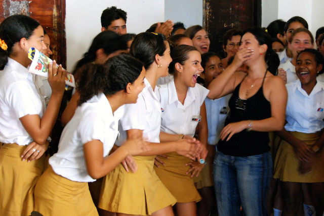 School girls laugh with their teacher in Trinidad, Cuba.