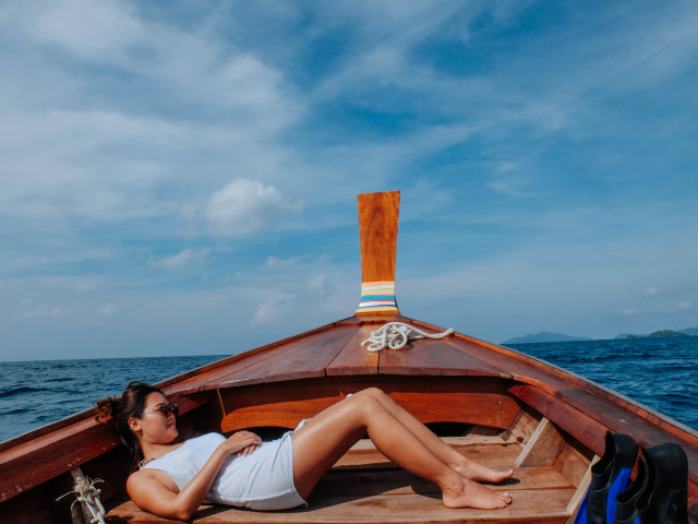 a woman lie flat on wood boat