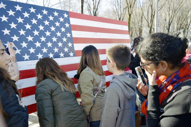 People signing an American Flag board at the Women's March in Chicago during the civil protest