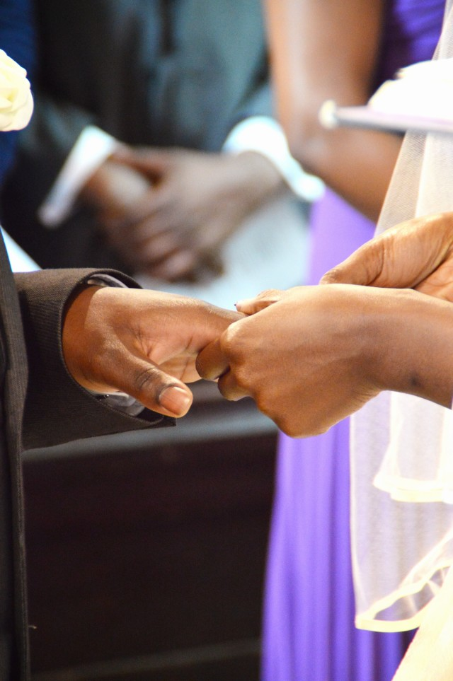 Bride putting the ring on her groom's finger