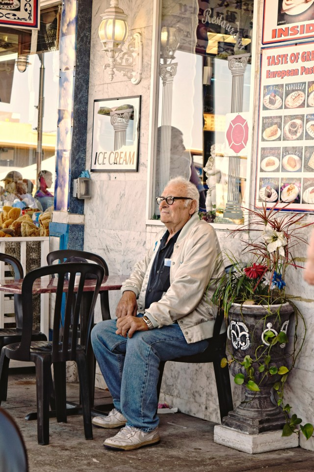 Old man reflecting outside a Greek restaurant at an outdoor cafe