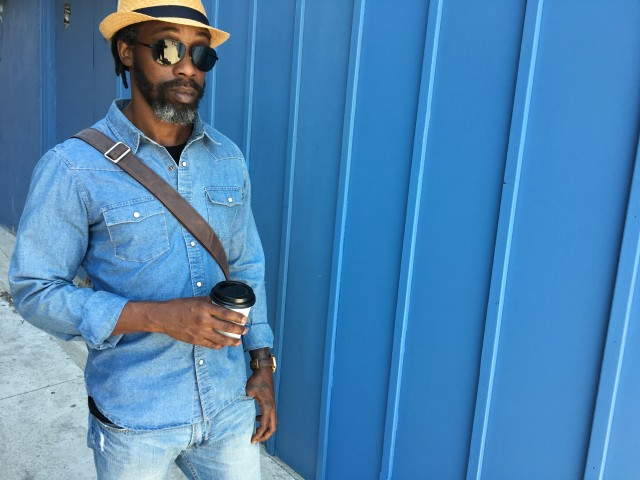 Stylish man wearing denim shirt and holding a coffee cup against Bright blue background wall