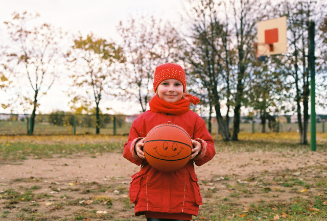 Little girl smiling and keep in her hands a ball after practice.