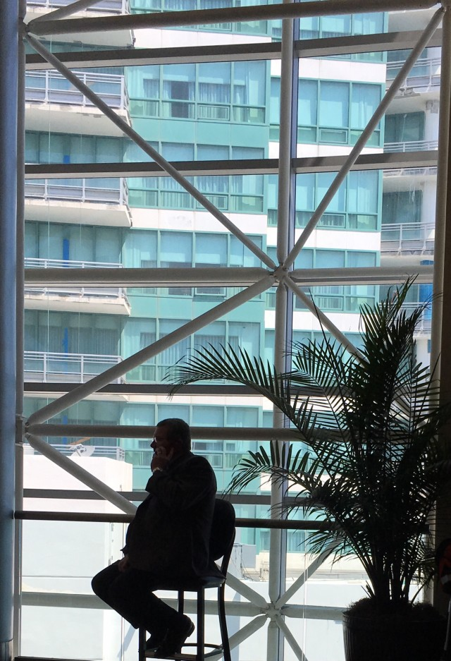 Silhouette of a businessman on a phone a a conference against a colorful geometric window