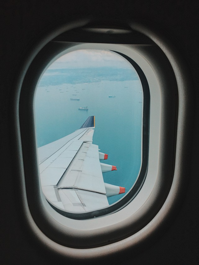 View of plane's wing, ships and island from my seat.