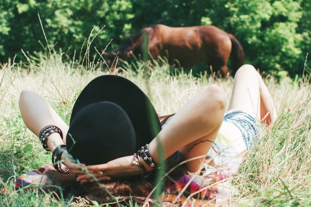 Girl in hat laying on the grass