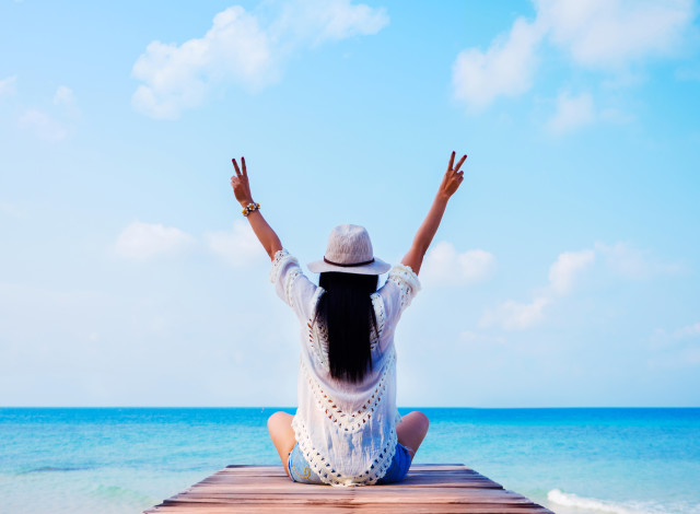 Woman in sunhat with raised hands sitting and looking at sea.