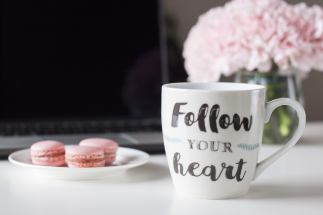 A coffee mug with words that say follow your heart on a desk with pink macaroons and pink flowers in Background