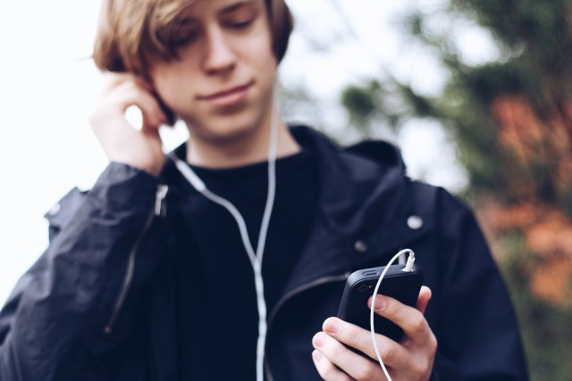 The young man listens to music in earphones on the iPhone