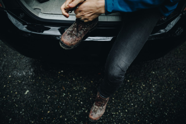 A man, wearing a wedding ring, ties his muddy boots while sitting in the back of a black car