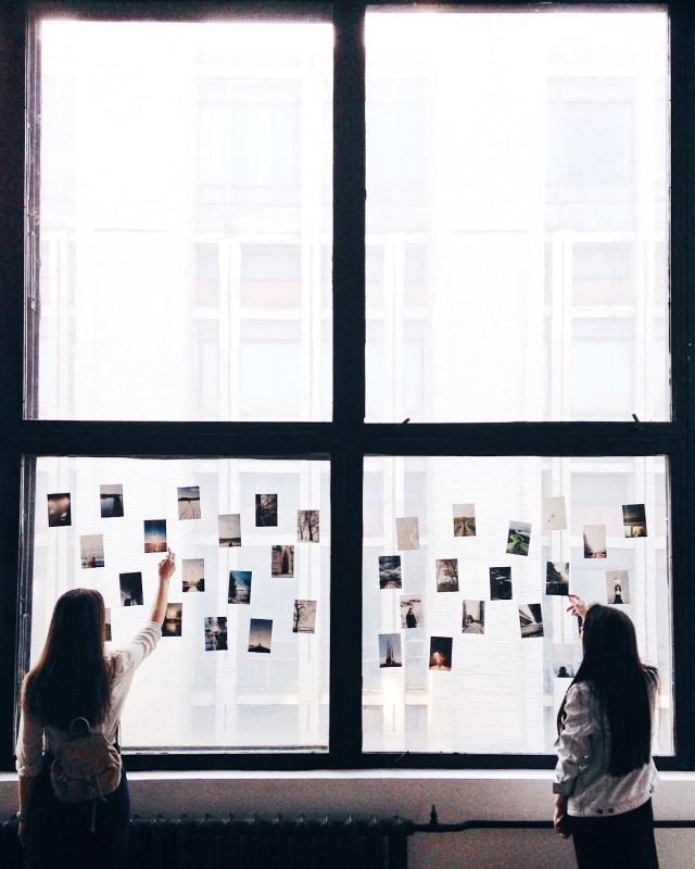 Two girls looking photos on the window
