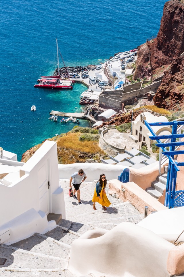 Couple walking up steep stairs from beautiful blue sea below, Santorini Greece