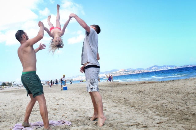 2 guys swinging a girl on the beach