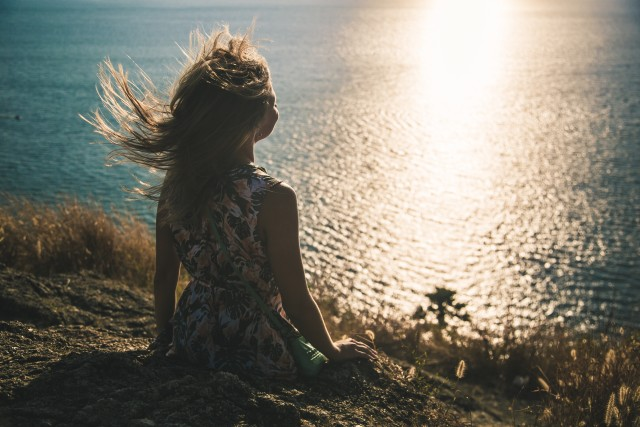 Girl watching sunset and wind playing with her hair