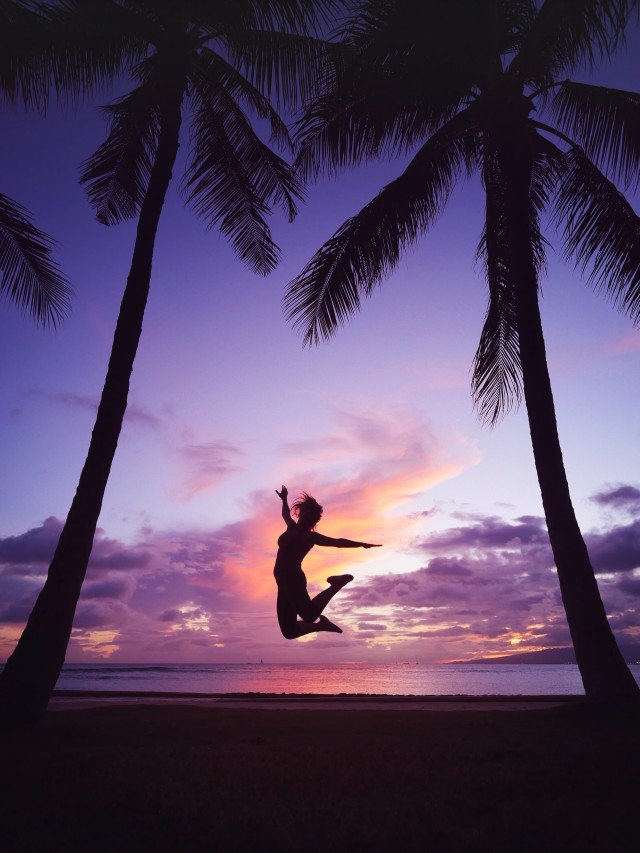 Hawaii magic hour purple sunset dancing happy jump between two palm trees on the tropical beach