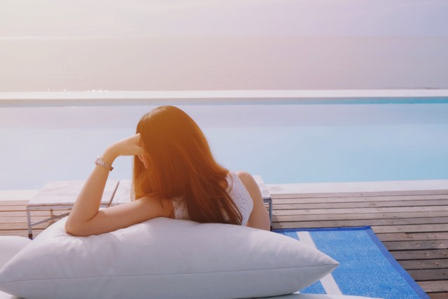 Woman feeling relax on bean bag nearby the swimming pool at the luxury resort