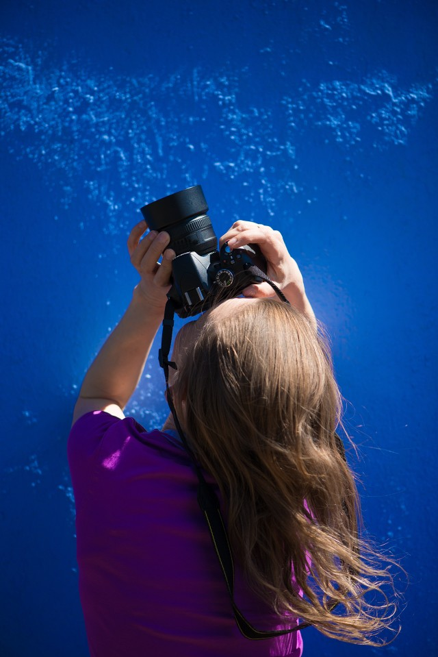 A portrait of a female photographer on a monochrome blue background