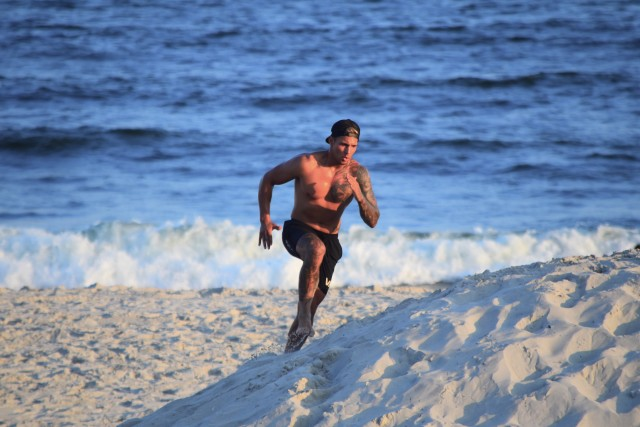 Young very fit bare chested millennial male with tattoos running up a sand dune at the beach with the ocean waves in the background.