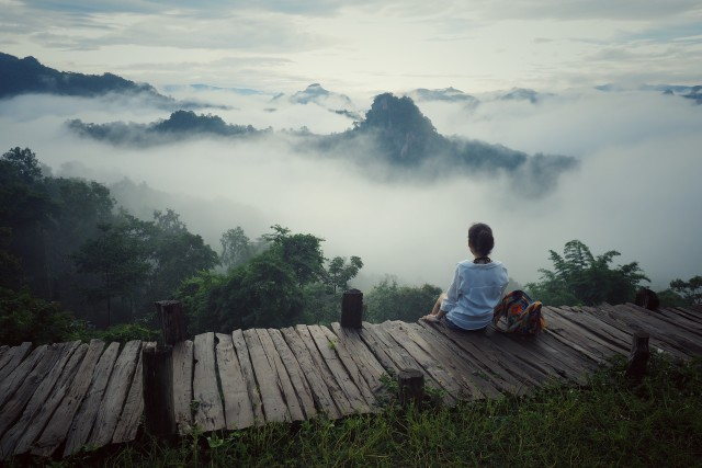 Woman is looking the fog over mountain view of Mae Hong Son, Thailand.