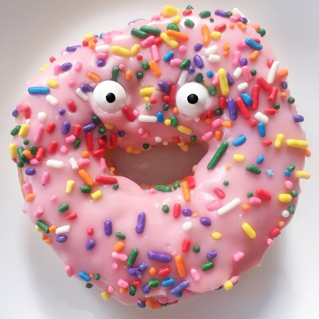Googly eyes on a pink sprinkled donut.