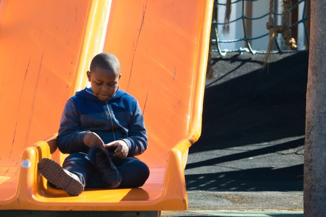 Little African boy tying his shoelace on a slide at the V&A Waterfront, Cape Town