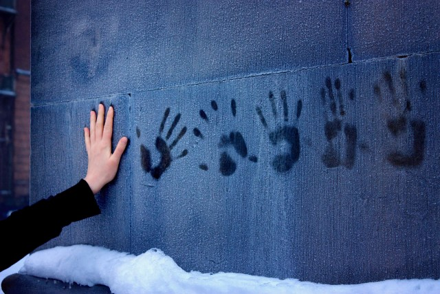 A woman's hand, leaving prints on a frozen wall