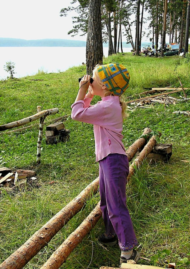 Little girl looking through binoculars at lake