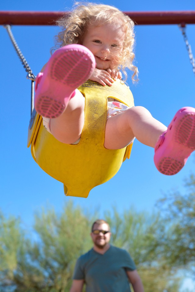 Toddler girl swinging high up in the air with Dad in background at playground