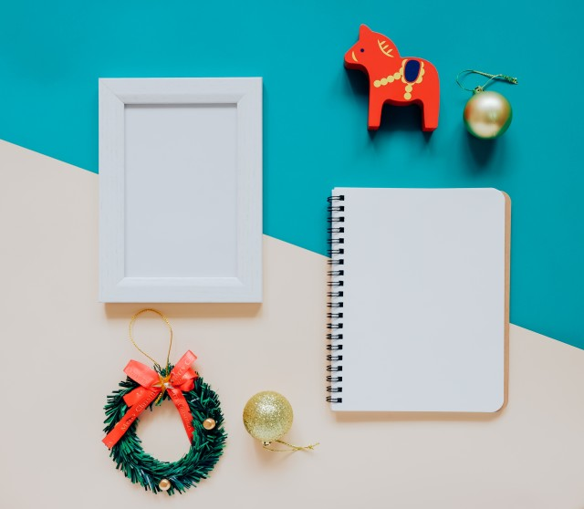 Creative flat lay of craft and photo frame, blank notebook mock up with christmas ornaments and gift box on colorful background, minimal style