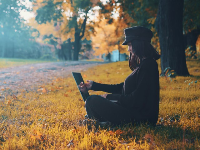 Beautiful woman working on laptop in autumn park