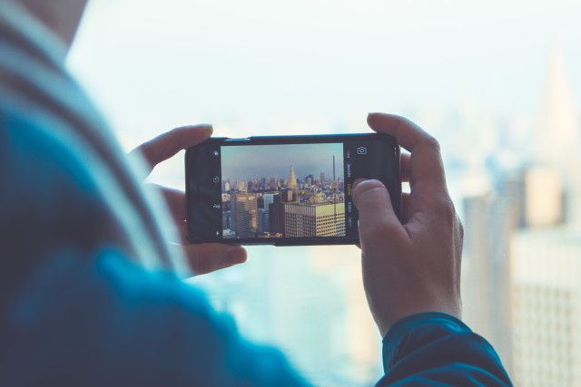Using a mobile phone to take photos of a cityscape
