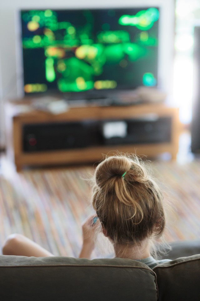 Back view of young blonde girl relaxing and playing video game sitting on sofa in front of tv screen at home