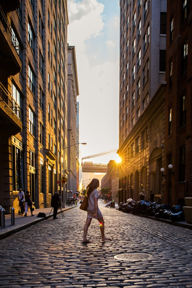 golden sun backlights in brooklyn with girl crossing street