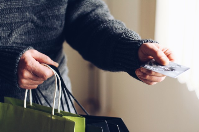 man holding shopping bags and handing credit card
