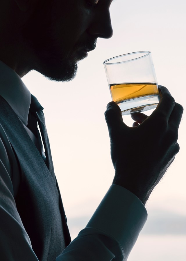Professional businessman drinking a neat whiskey alcoholic drink silhouetted by bright window