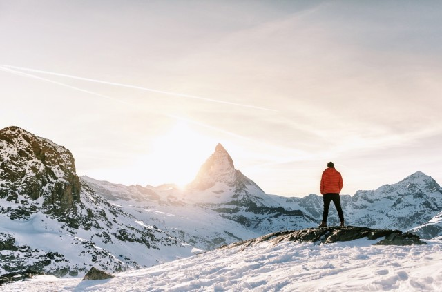 Man standing in the alps in Switzerland in front of the Matterhorn