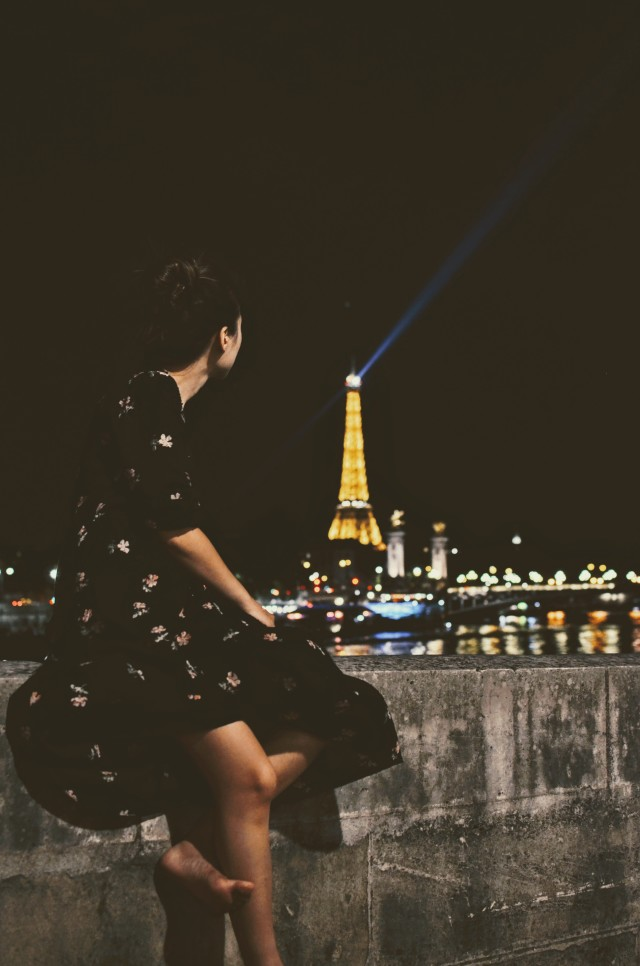 Beautiful girl watching the lights on the Eiffel Tower at the top of the hour.