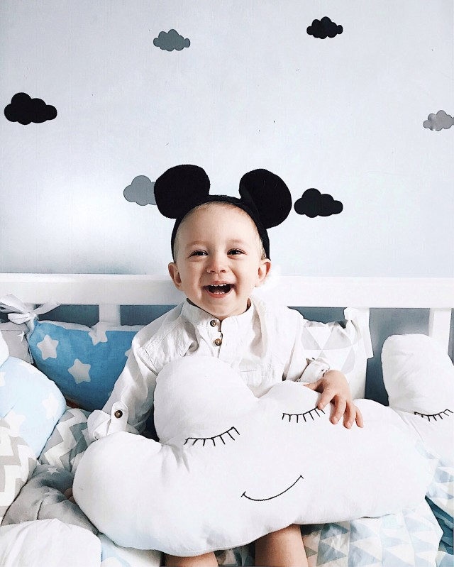 Smiling boy sitting on the bed with toy clouds ☁️