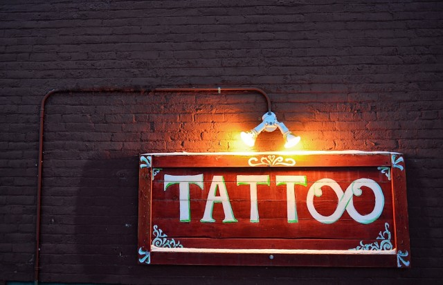 Words in the wild - tattoo sign on a brick wall with space for copy, illuminated at night