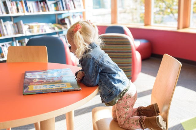 Little preschool aged girl with blond pigtails at the library looking at a book  💫