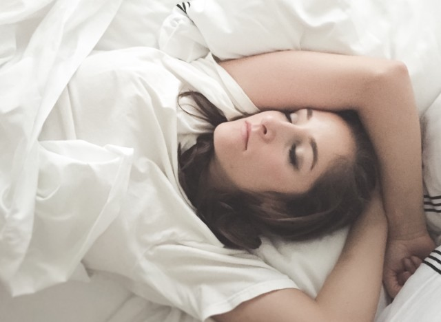 Young woman sleeping in bed with white sheets