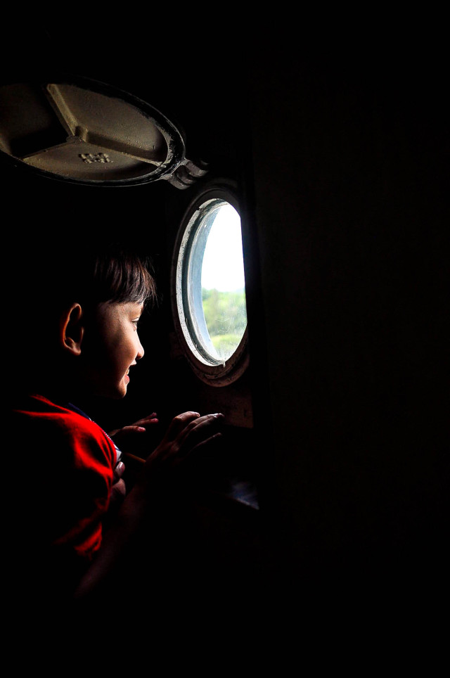 A young boy looking into small window in a ship.
