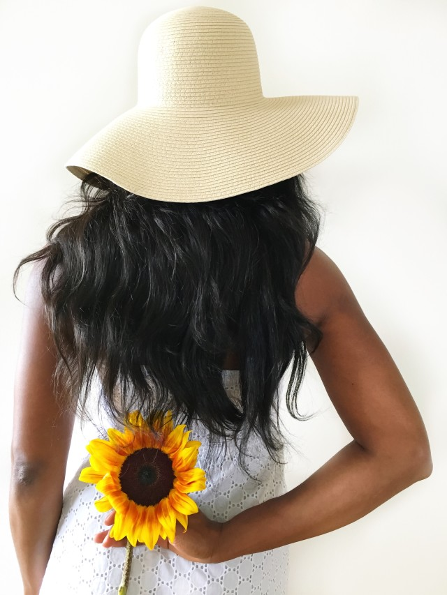 Summertime - diverse Woman in a big sunhat holding a sunflower behind her back