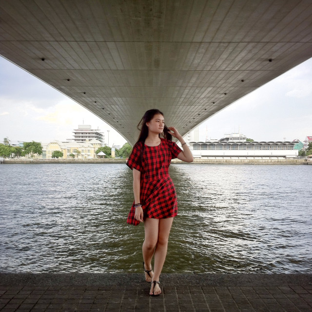 A girl standing under the bridge