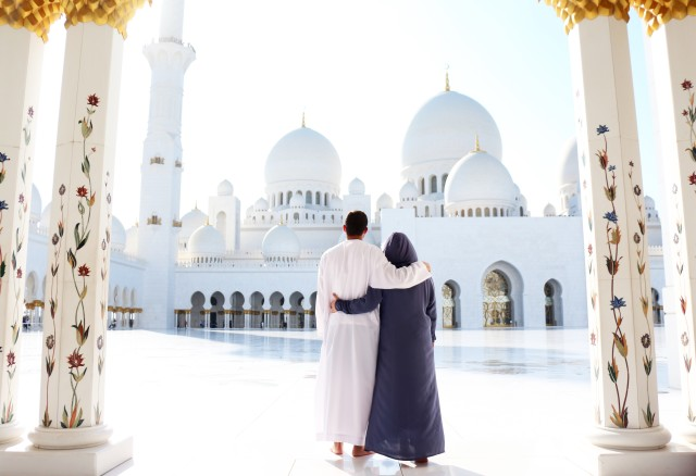 Travel: A Couple from behind at the Abu Dhabi white mosque.