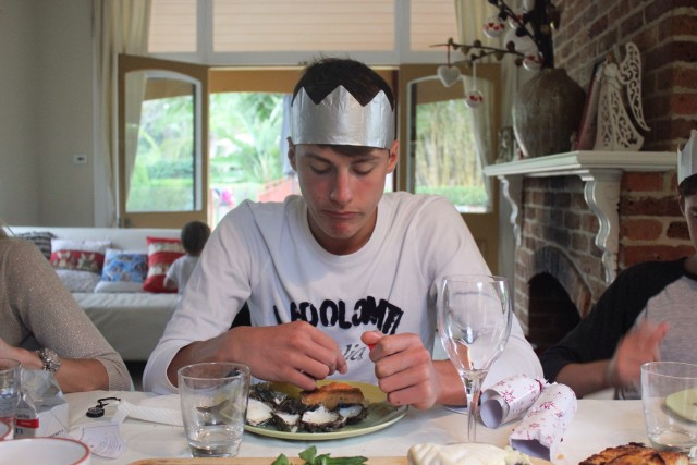 teenager wearing a silver paper crown sitting at christmas dining table