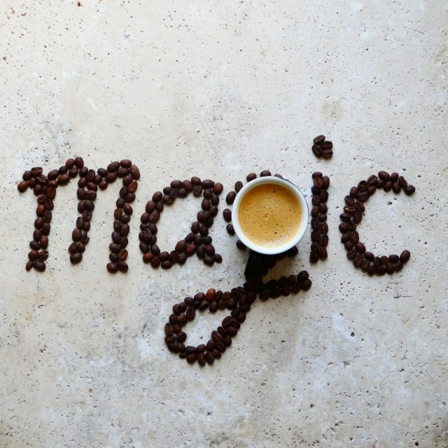 magic in every cup ,word art made with coffee beans and coffee on stone table ,coffee bean art, coffee words,text made with coffee beans,typography