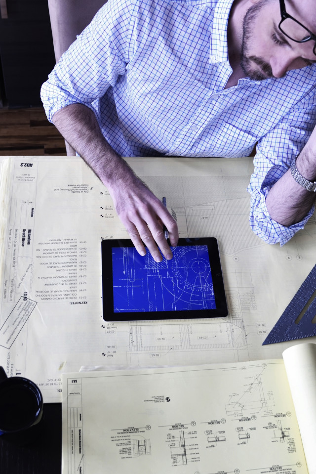 Overhead man using a mobile tablet Apple iPad device on desk with design blueprints and other tools. Vertical orientation. RLTheis